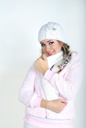 The young beautiful girl in a white cap and a scarf on a white background  Stock Photo - 16788423