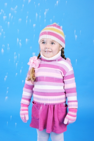 the little girl in a sweater and a hat with the snow Stock Photo - 16891053