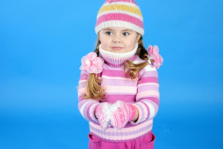and he shines: the little girl in a sweater and a hat with the snow
