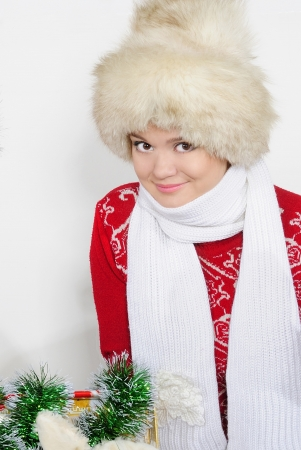 The young beautiful girl in a fur cap and a red sweater photo