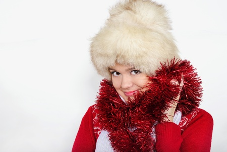 The young beautiful girl in a fur cap on a white background with New Year photo