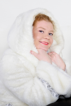 The young beautiful girl in a fur cap on a white background with a New Year photo