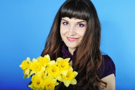 briliance: Beautiful smiling girl with long hair with yellow narcissus on blue background