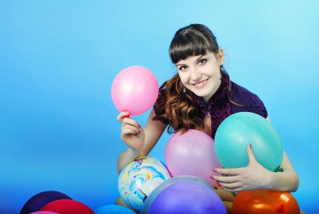 briliance: Beautiful smiling girl with long hair on blue background with air ball