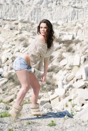 cogitation: beautiful girl on stone coast near lake Stock Photo
