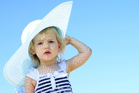 a little girl in large hat on the shore of the sea in the summer Stock Photo