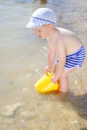 a little boy playing on the sea-shore in summer Stock Photo - 18485862