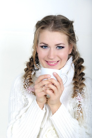 The young beautiful girl in a white scarf with a mug Stock Photo - 22473027