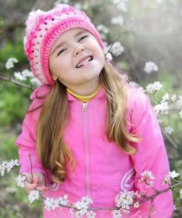 beautiful little girl near a flowering tree Stock Photo