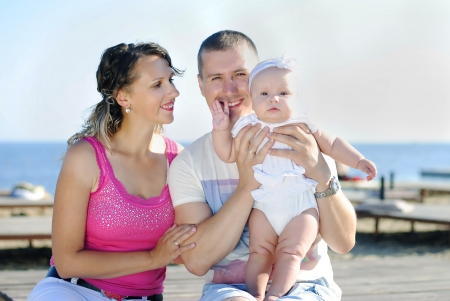 the little girl with her parents near the sea