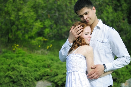 beautiful young couple in love middle of a green meadow with blue flowers  photo