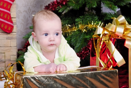 small breast child boy lies near new years fir tree with gift  photo