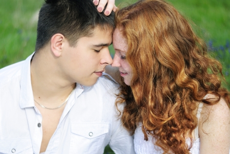 beautiful young couple in love middle of a green meadow with blue flowers
