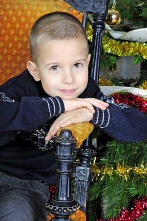 boy near a Christmas tree with presents photo