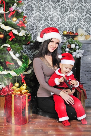 kinky: a little boy near the tree with her mother in a Santa suit