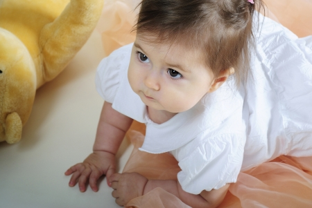 attentiveness: The small beautiful girl lies on a white with toys Stock Photo