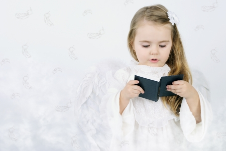 A beautiful little girl angel with a book photo