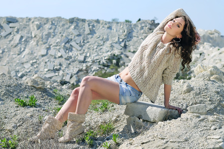 beautiful girl on stone coast near lake  photo
