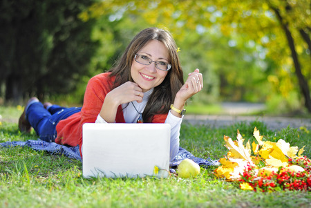 green office: young beautiful girl on a green meadow with a computer