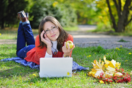 young beautiful girl on a green meadow with a computer
