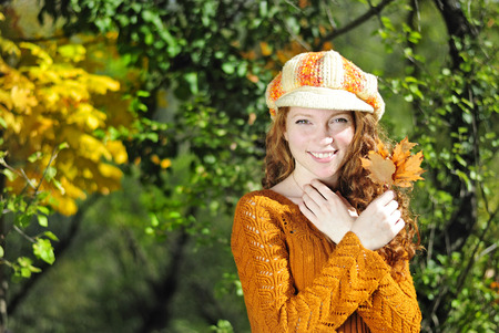 Young beautiful red-haired girl in the autumn park
