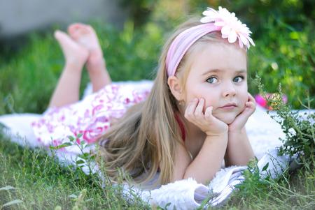 pretty little girl lying on green grass in summer