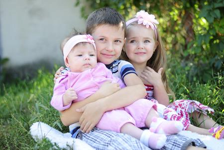 Three kids sitting near flowers