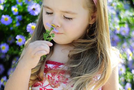 pretty little girl near a bush of flowers