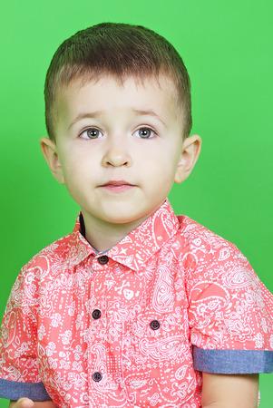 small pretty boy on green background Stock Photo