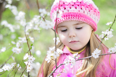 beautiful little girl near a flowering tree Stock Photo