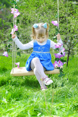 little girl on green grass in the spring in a Blue Dress Stock Photo