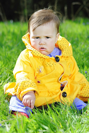 little girl on a green meadow in a bright yellow jacket