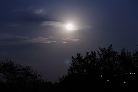 Luna in nightly sky in clouds Stock Photo