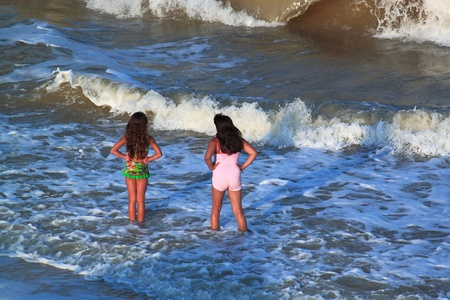 Children look at-sea on appearing suddenly waves