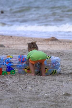 A little boy on a marine beach  plays with toys