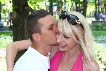 A boy kisses a beautiful girl blonde