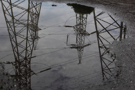 Reflection power lines in rain puddle Stock Photo