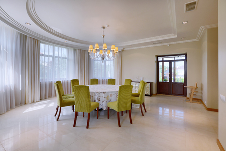 Interior of modern living room in a spacious apartment in bright colors with large dining table.