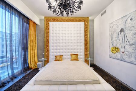 Designer modern renovation in a luxury house. Stylish bedroom interior with double bed.
