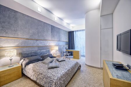 Modern design bedroom interior in gray and blue tones in a luxurious apartment.