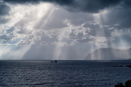 The suns rays through the clouds over the black sea coast. Novorossiysk. The Village Of Shirokaya Balka