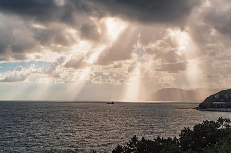 The sun's rays through the clouds over the black sea coast. Novorossiysk. The Village Of Shirokaya Balka Фото со стока