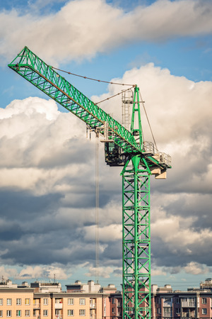 Green tower crane on the background of the neighborhood and the cloud sky. Close-up and natural light