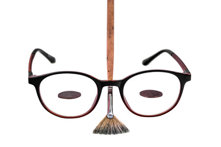Glasses and writing brushes isolated on white background, close-up. 版權商用圖片