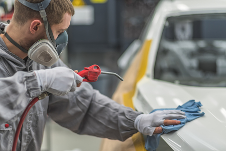 Employee car body painting shop prepares the surface for painting, removes dust Stock Photo