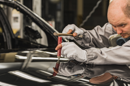 An employee of the car body painting shop eliminates a small metal defect with a special hand tool