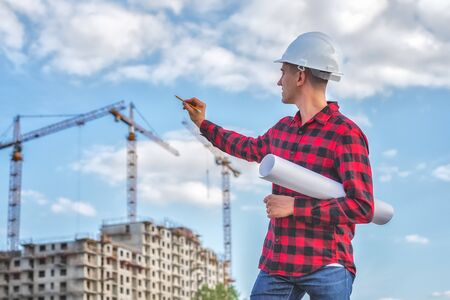 civil engineer in a white helmet on the background of houses under construction.