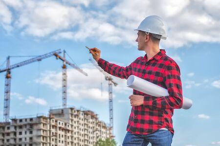 ingegnere civile in un casco bianco sullo sfondo delle case in costruzione.