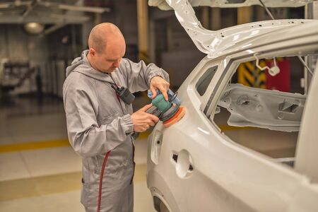 An employee of the car body painting shop polishes the painted surface with a pneumatic polishing machine