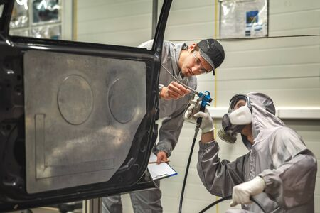 An employee of the paint shop of the automobile plant conducts training on applying sealant using a gun